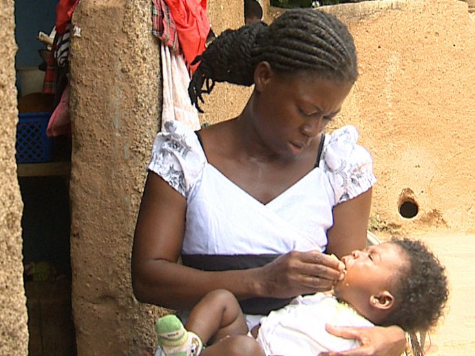Photo: mother administering SMC to baby